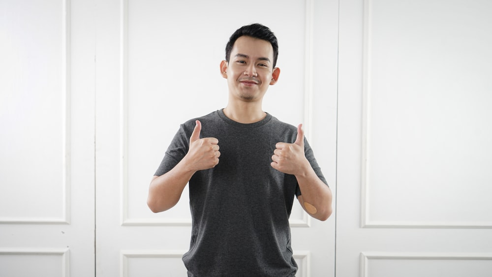 man in black tank top standing near white wall