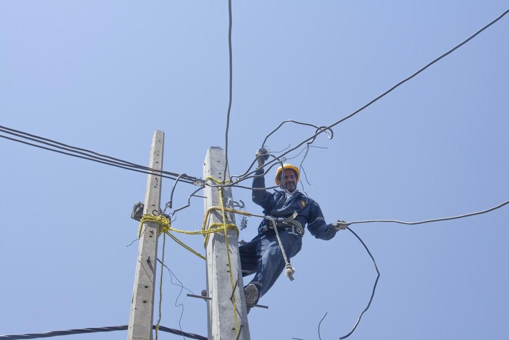 man in black jacket and black pants wearing black helmet on brown electric post during daytime