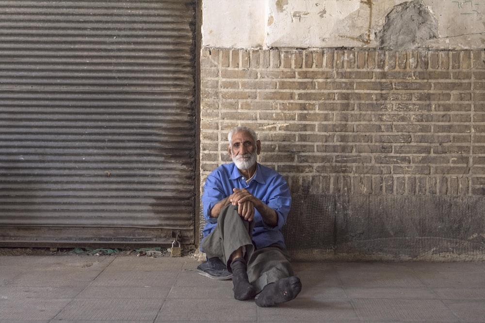 man in blue jacket sitting beside brown brick wall