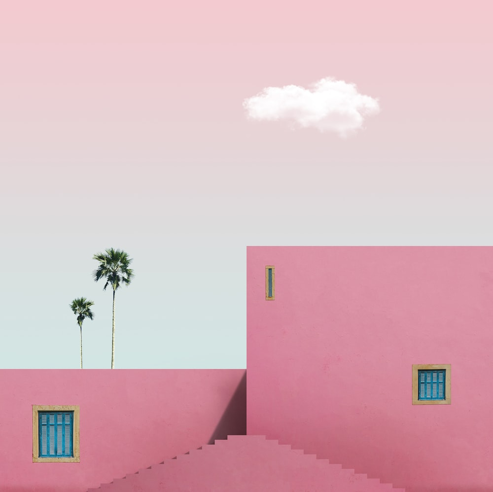 pink concrete building with palm tree in front