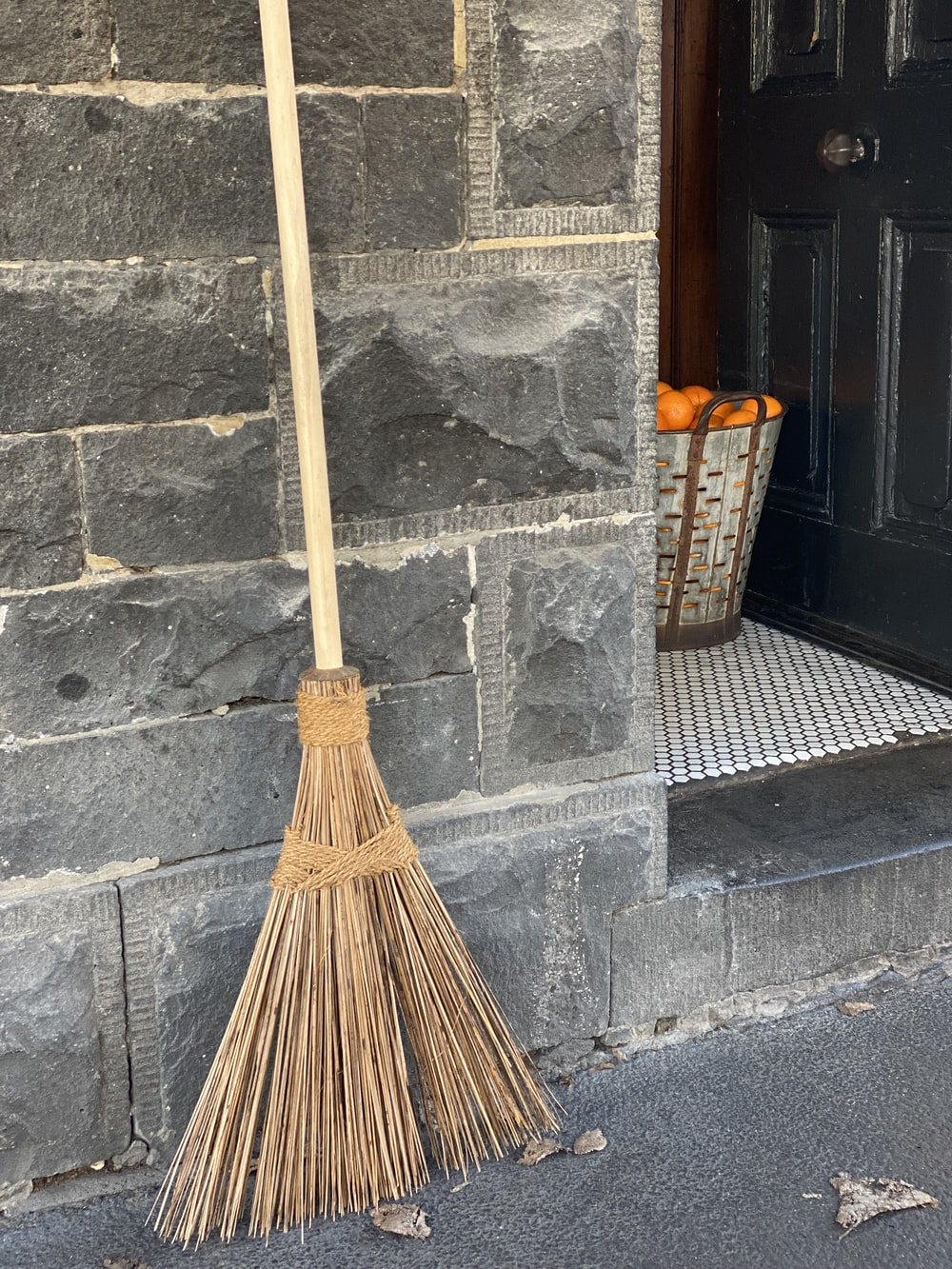 brown broom leaning on gray concrete wall