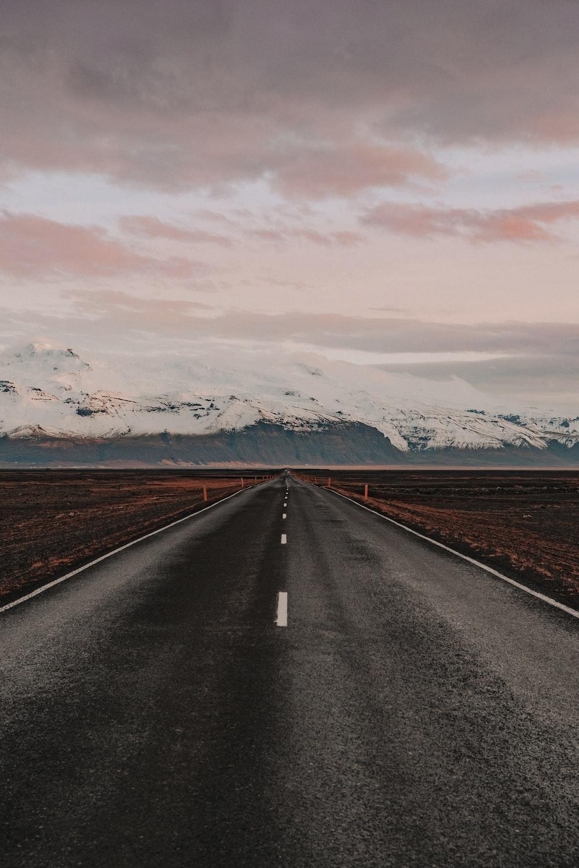 black asphalt road near snow covered mountains during daytime