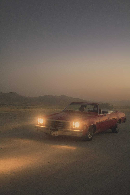 brown chevrolet camaro on desert during sunset
