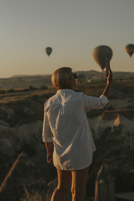 woman in white shirt holding white balloon during daytime