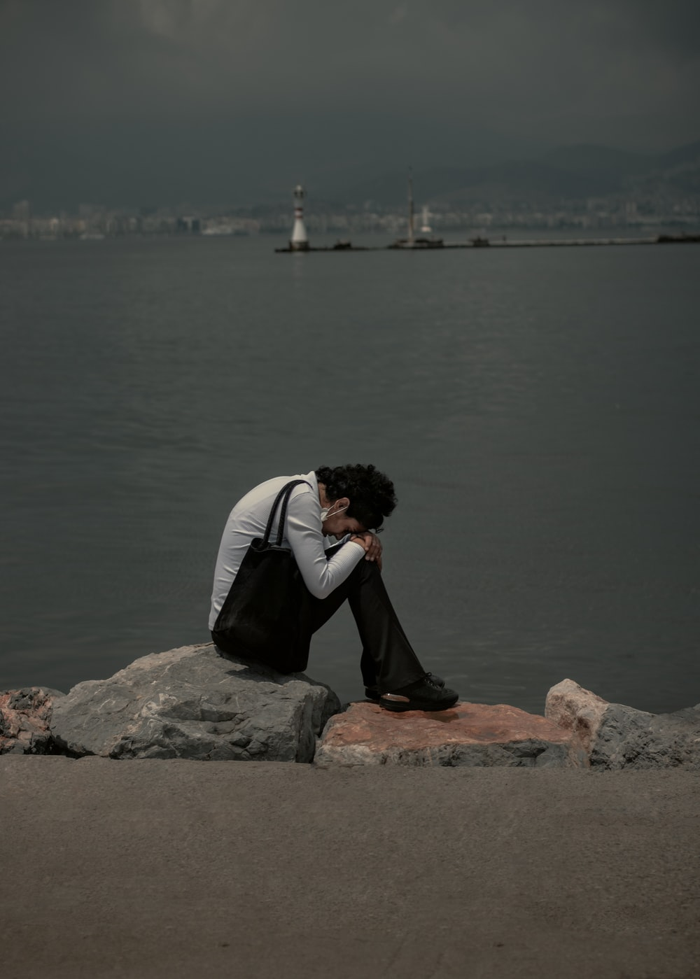 man in black and white jacket sitting on brown rock near body of water during daytime
