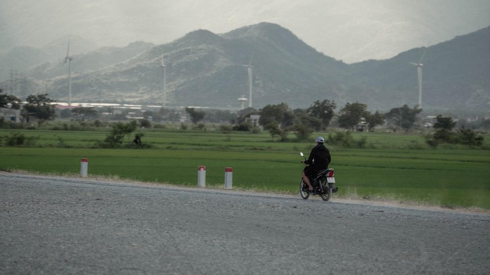 man in black shirt riding motorcycle on gray asphalt road during daytime