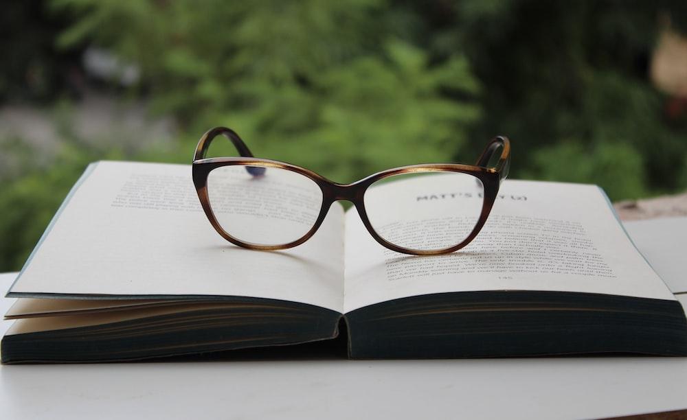brown framed eyeglasses on book page