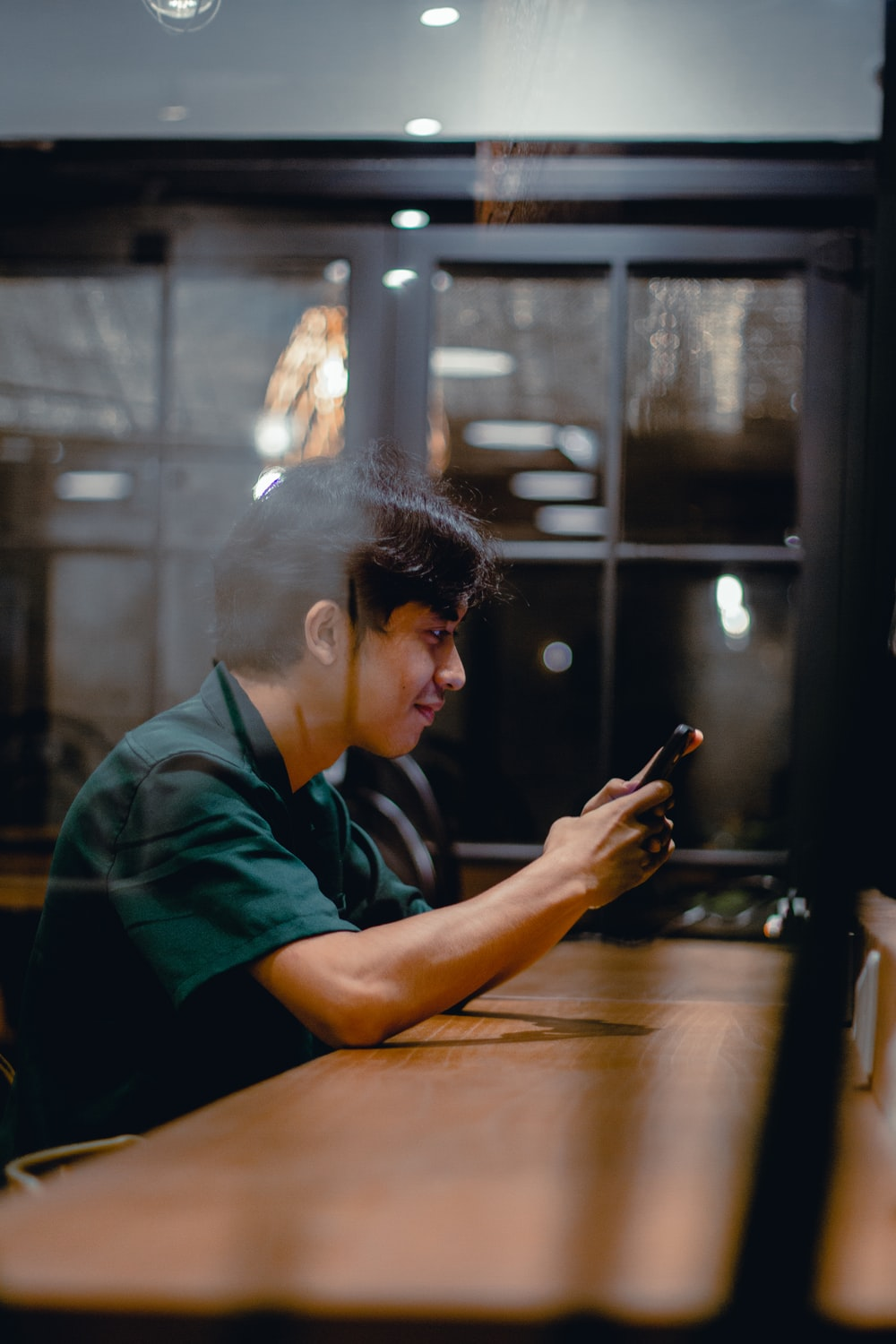 man in green polo shirt holding smartphone