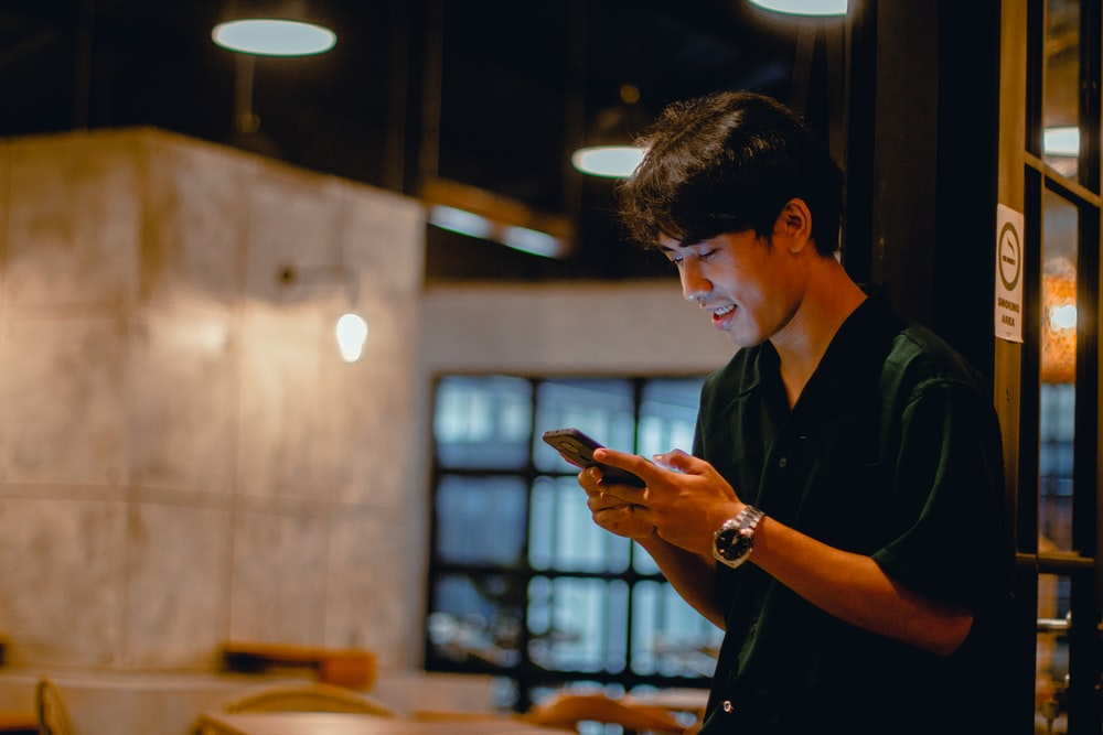 man in black polo shirt using smartphone