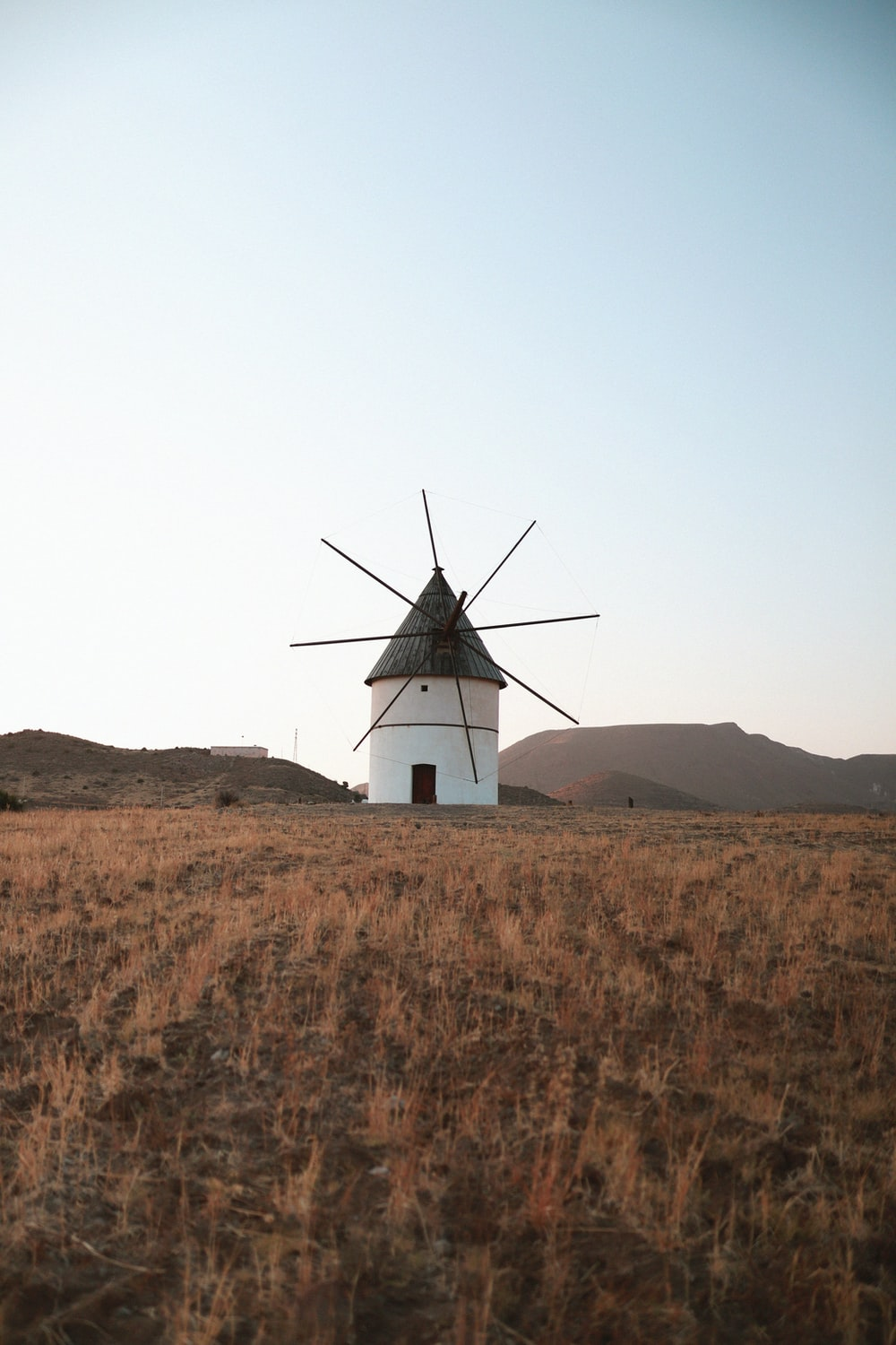 white and black windmill on brown field under white sky during daytime