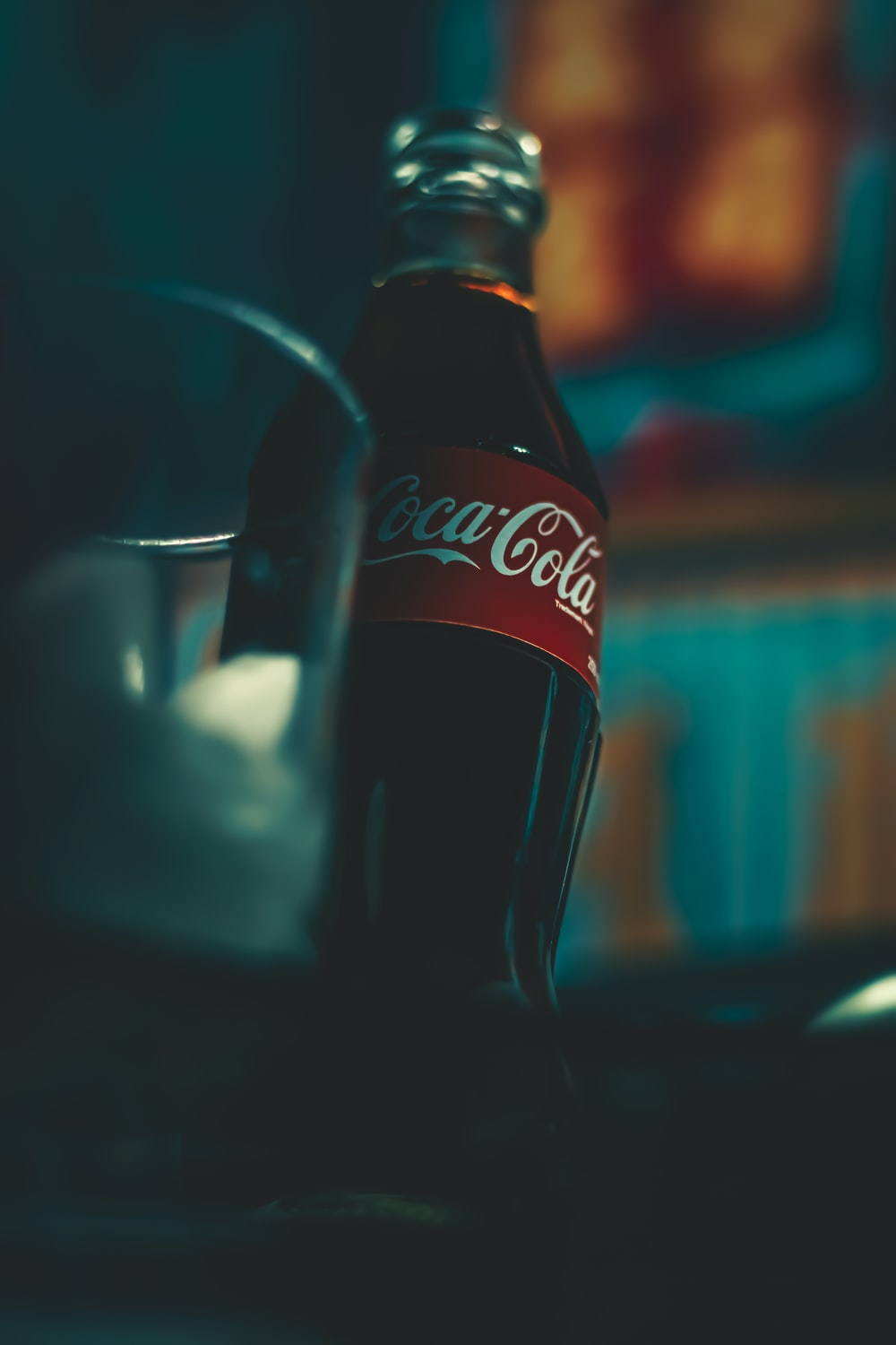 coca cola bottle beside clear drinking glass