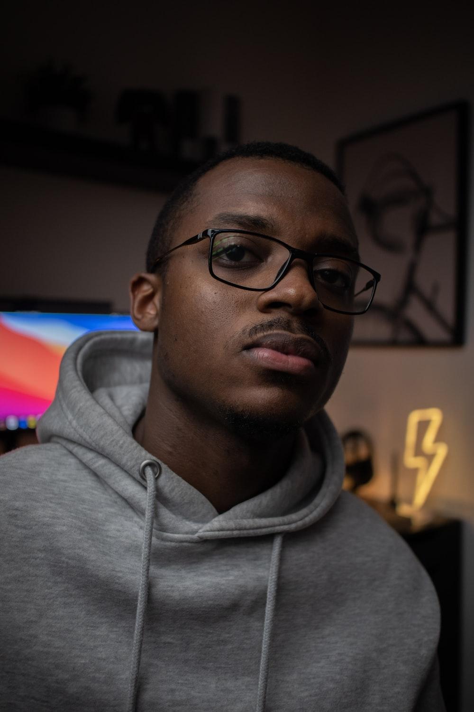 man in gray hoodie wearing black framed eyeglasses