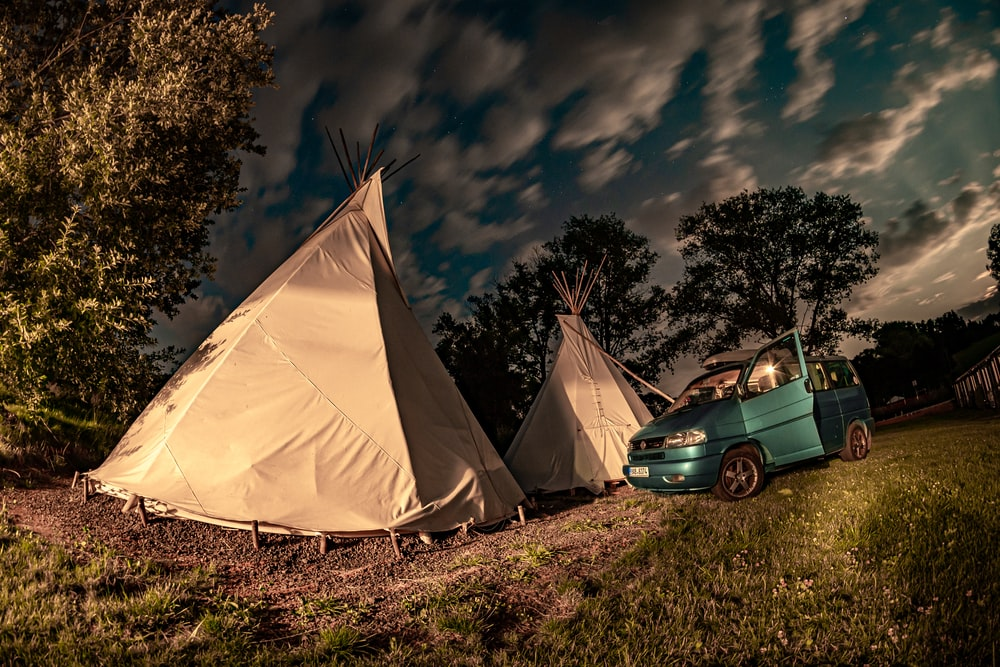 blue car parked beside white tent during night time