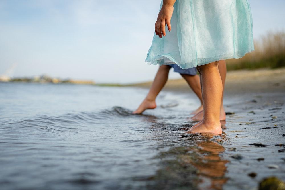 woman in teal dress walking on water