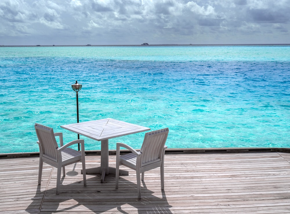 white wooden table and chairs on beach during daytime
