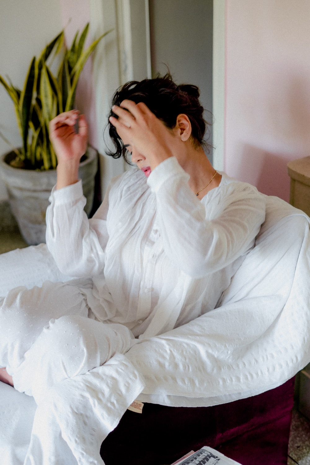 woman in white long sleeve shirt sitting on white bed