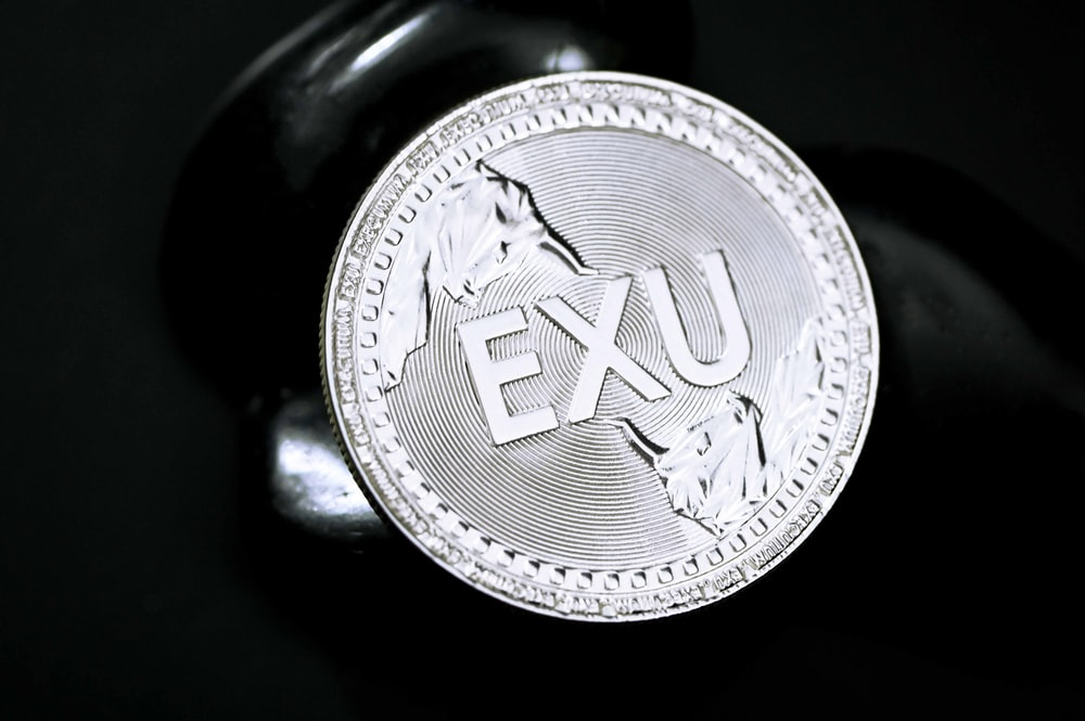 silver round coin on black surface