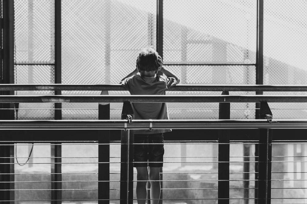 grayscale photo of woman in black jacket standing beside glass window