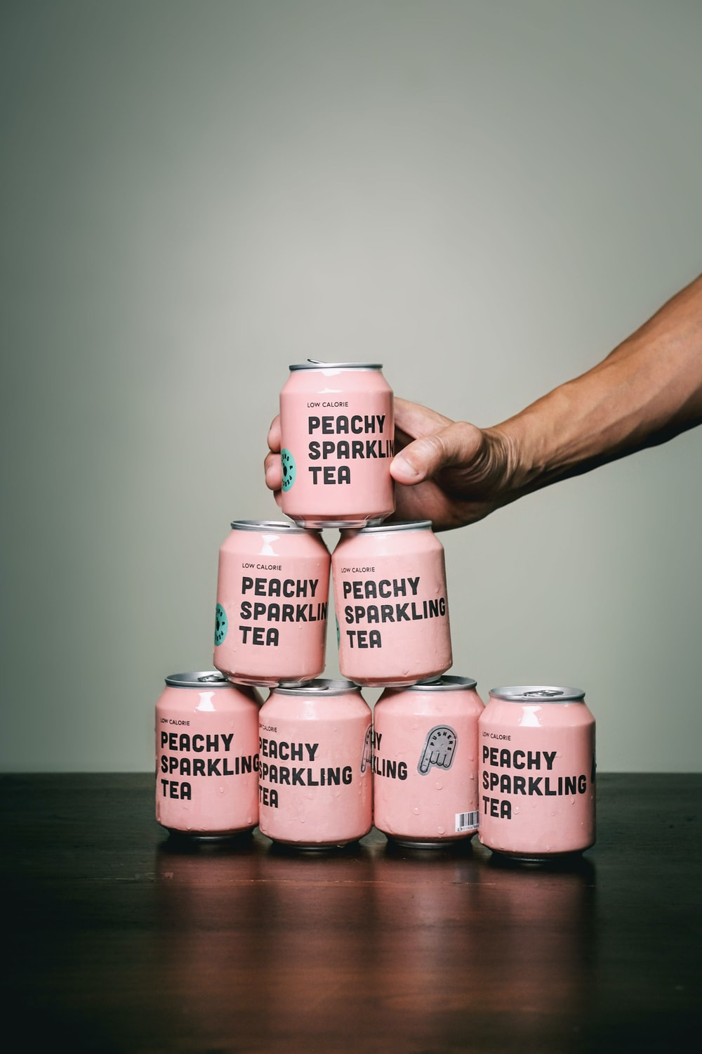 person holding pink and white labeled bottle