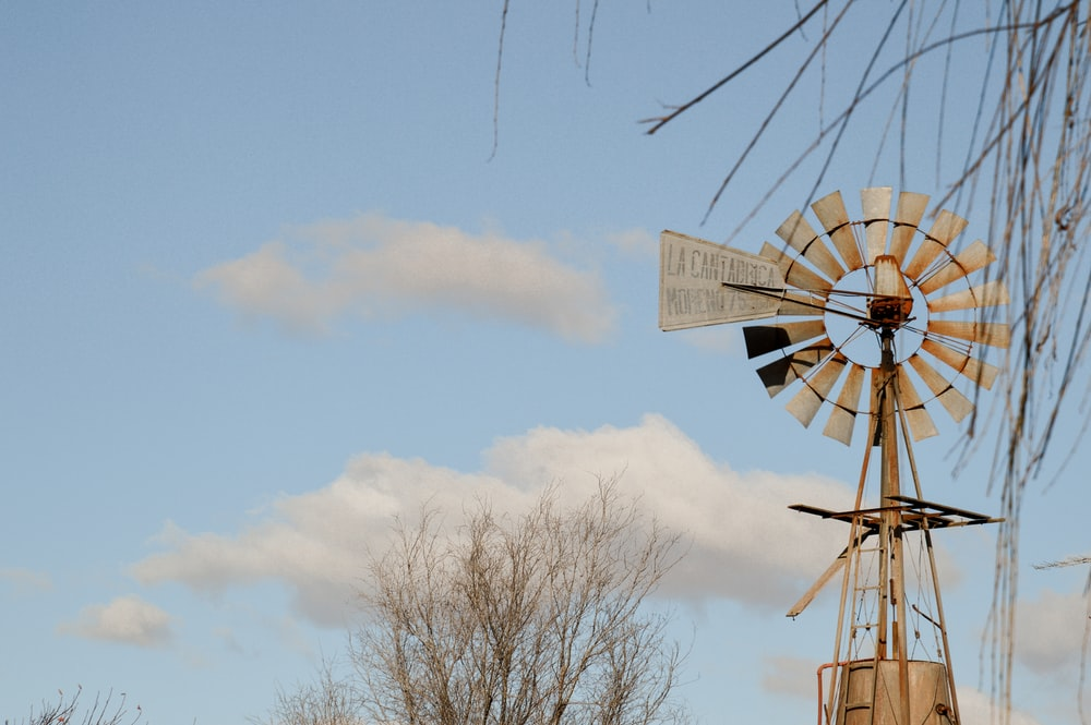 brown and white windmill under white clouds during daytime