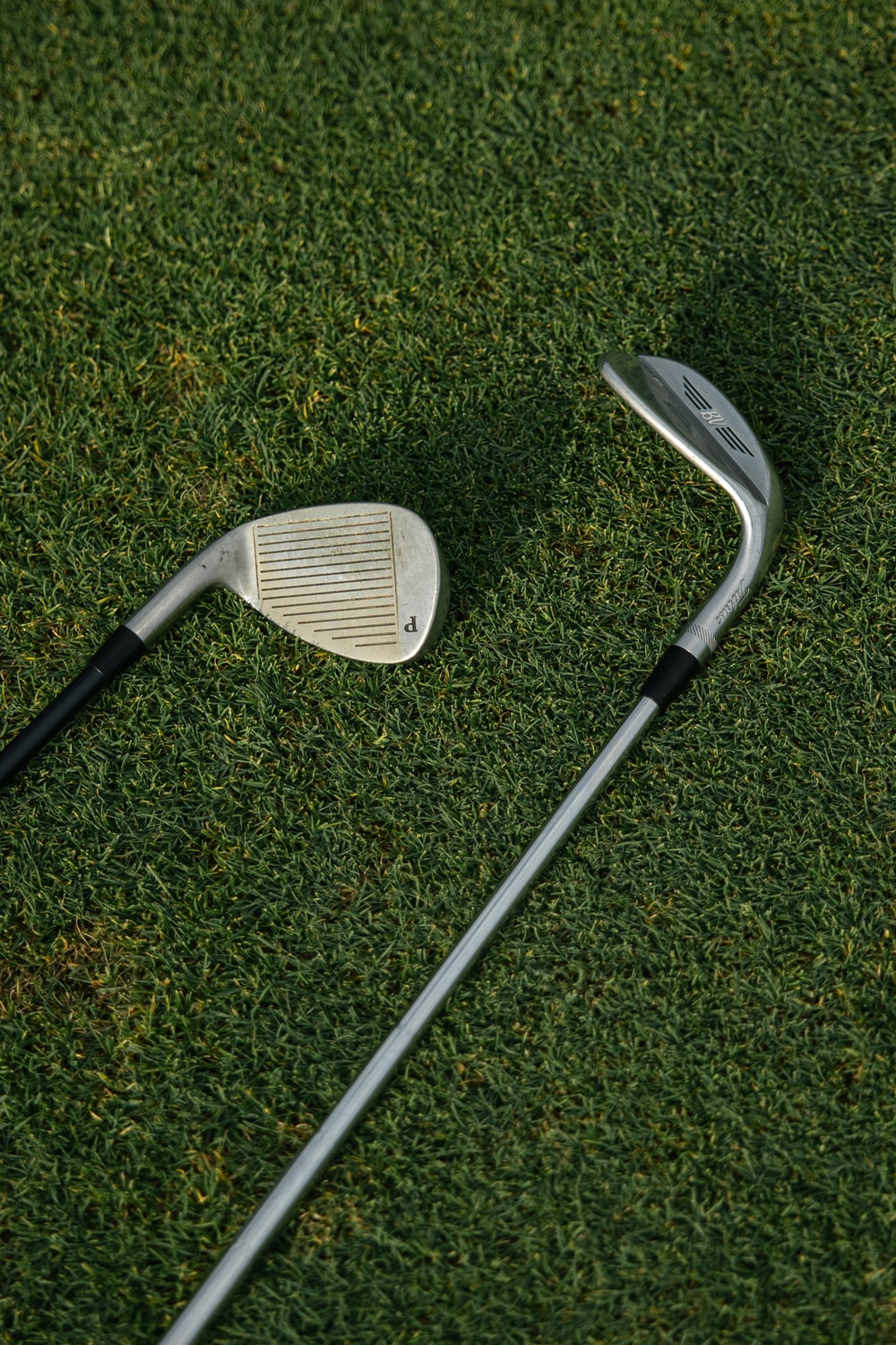 white and black golf club on green grass