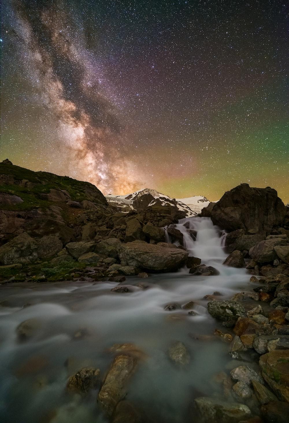 rocky mountain near body of water under starry night