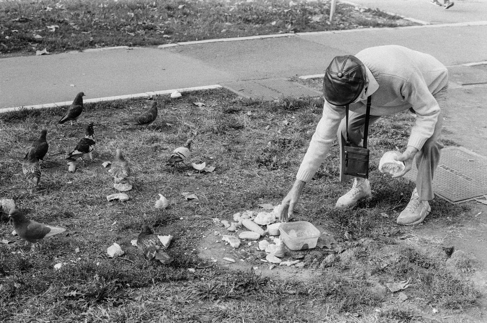 grayscale photo of man in t-shirt and shorts holding garbage bag