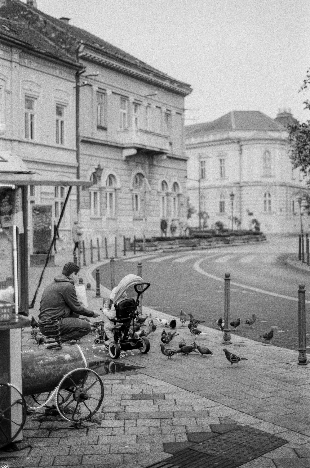 grayscale photo of man sitting on motorcycle in front of building