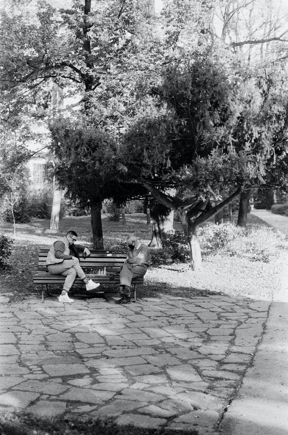 grayscale photo of 2 men sitting on bench near trees