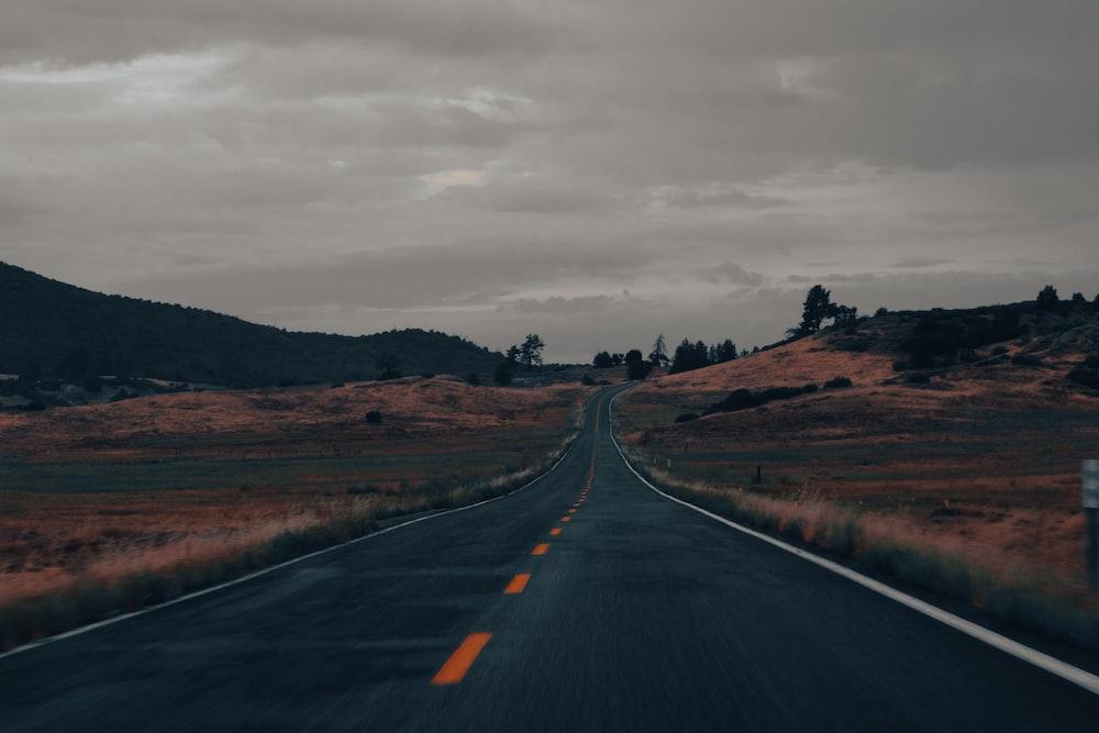 black asphalt road in between brown grass field under gray cloudy sky during daytime