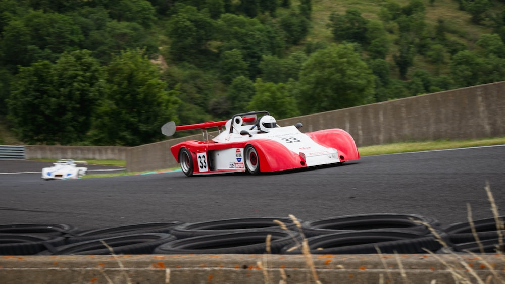 red and white racing car on track during daytime