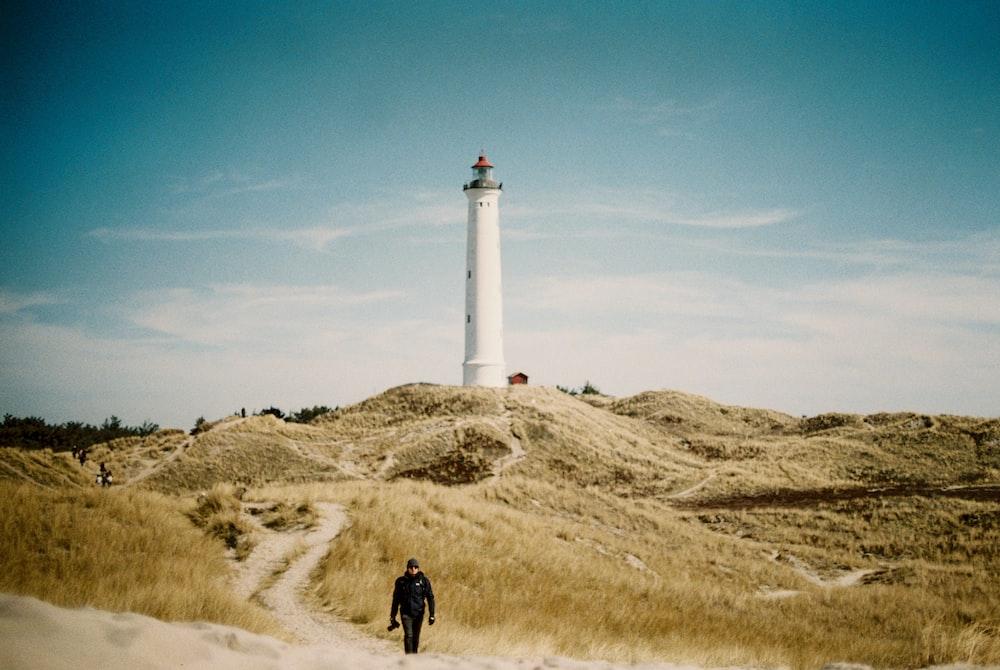 man in black jacket standing near white lighthouse under blue sky during daytime