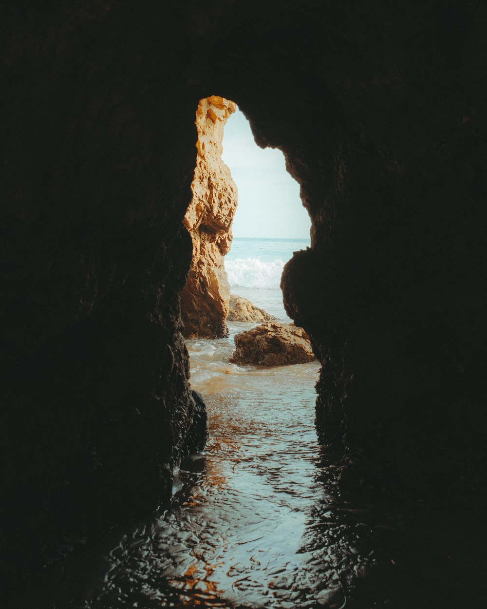 cave near body of water during daytime