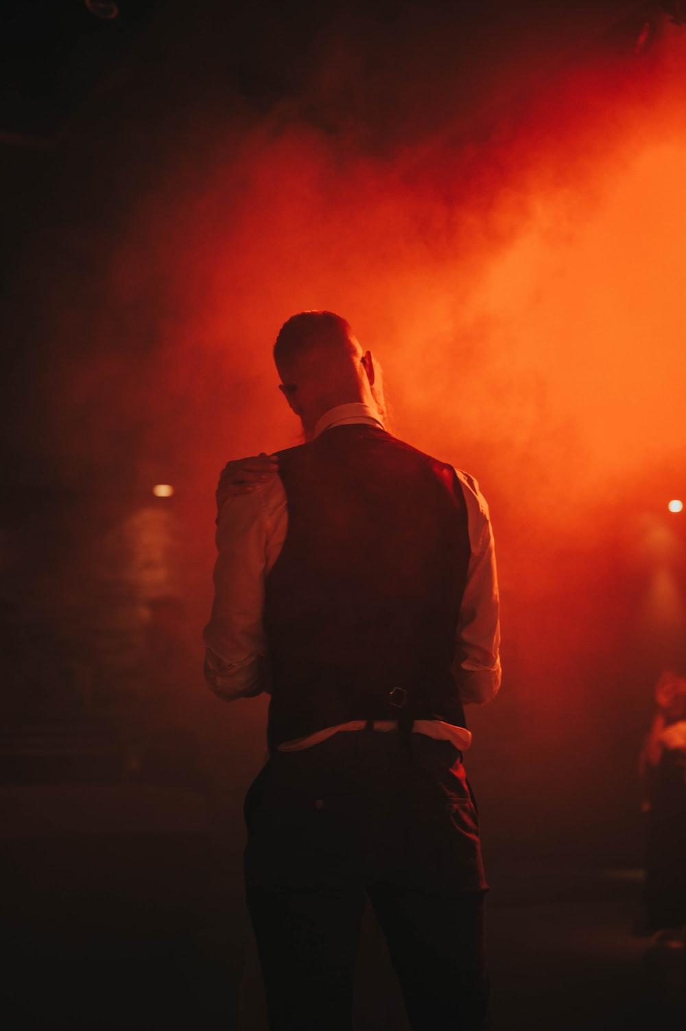 man in black vest standing on stage