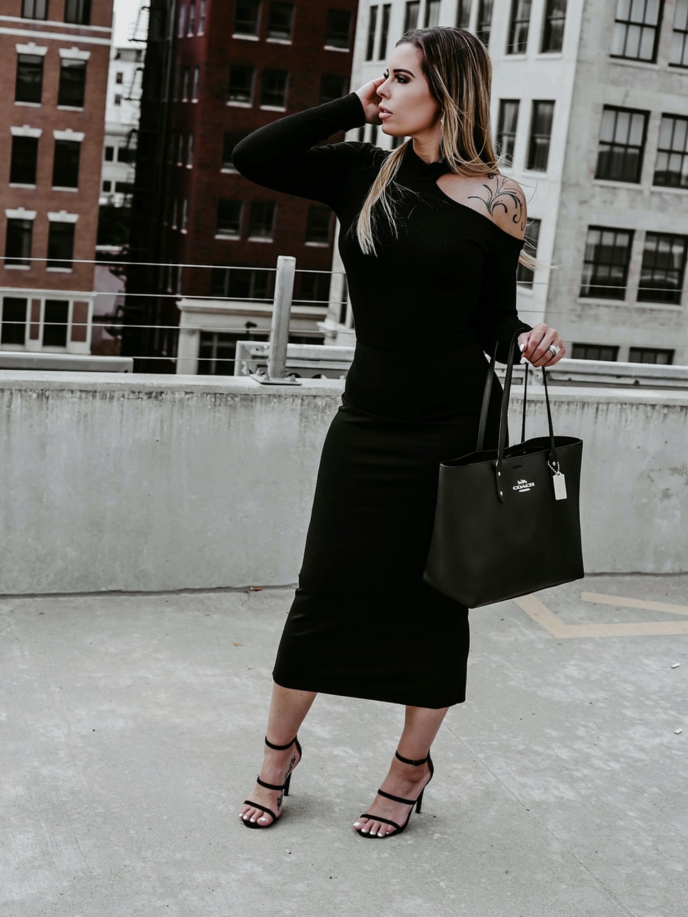 woman in black long sleeve dress holding black leather handbag