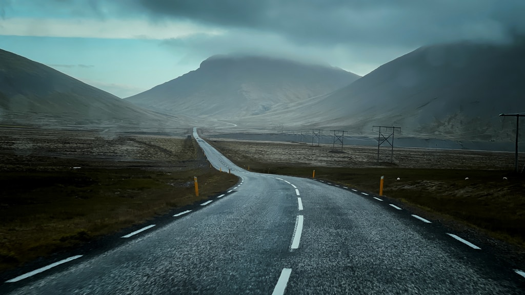 gray concrete road near mountain under white clouds during daytime