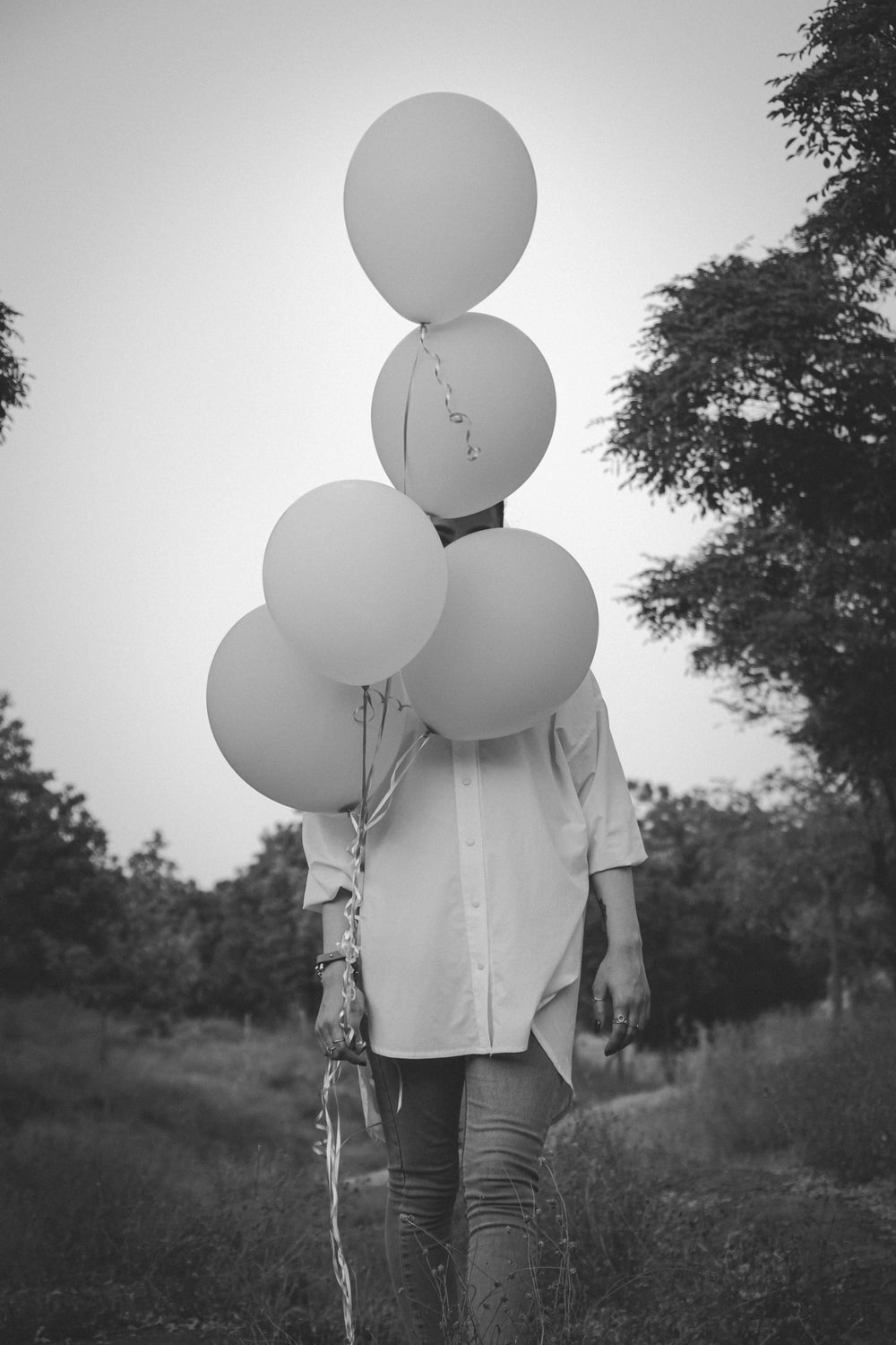 woman in white long sleeve shirt holding white balloons