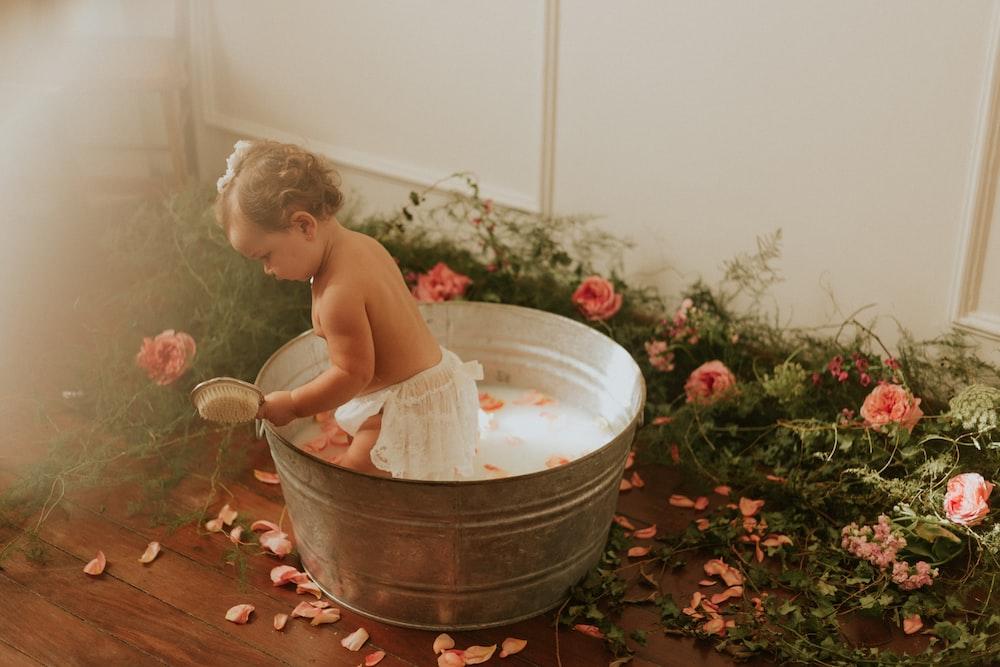 topless child sitting on white plastic bucket