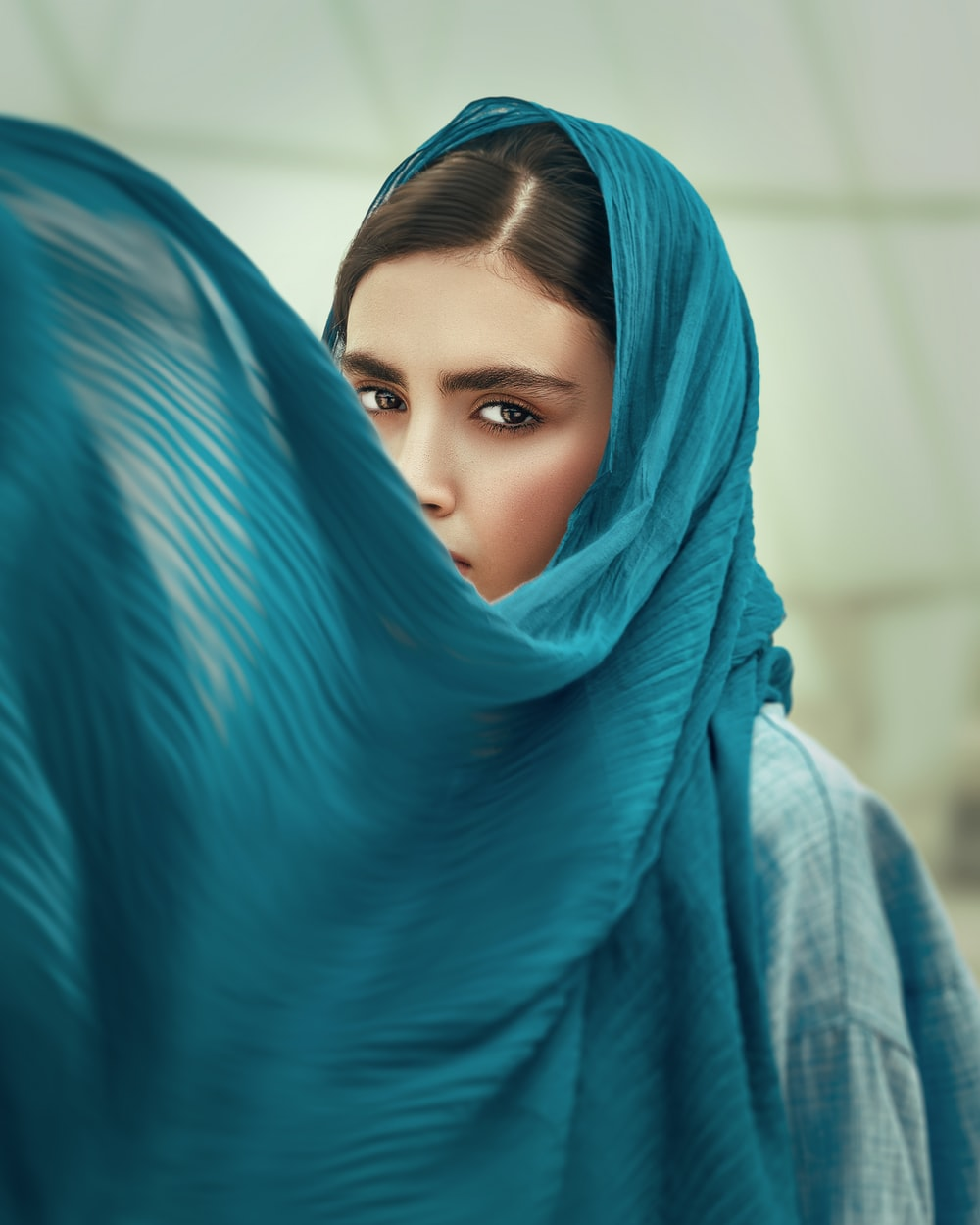 woman in blue hijab covering her face with blue textile