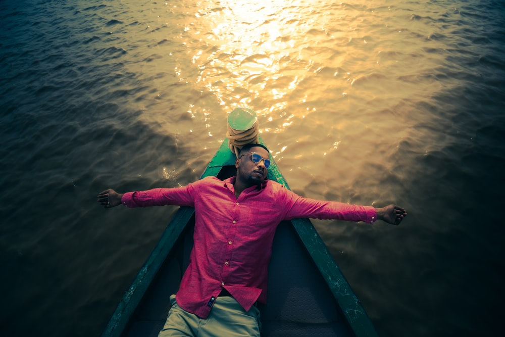 man in red and green jacket wearing green goggles on green boat during daytime
