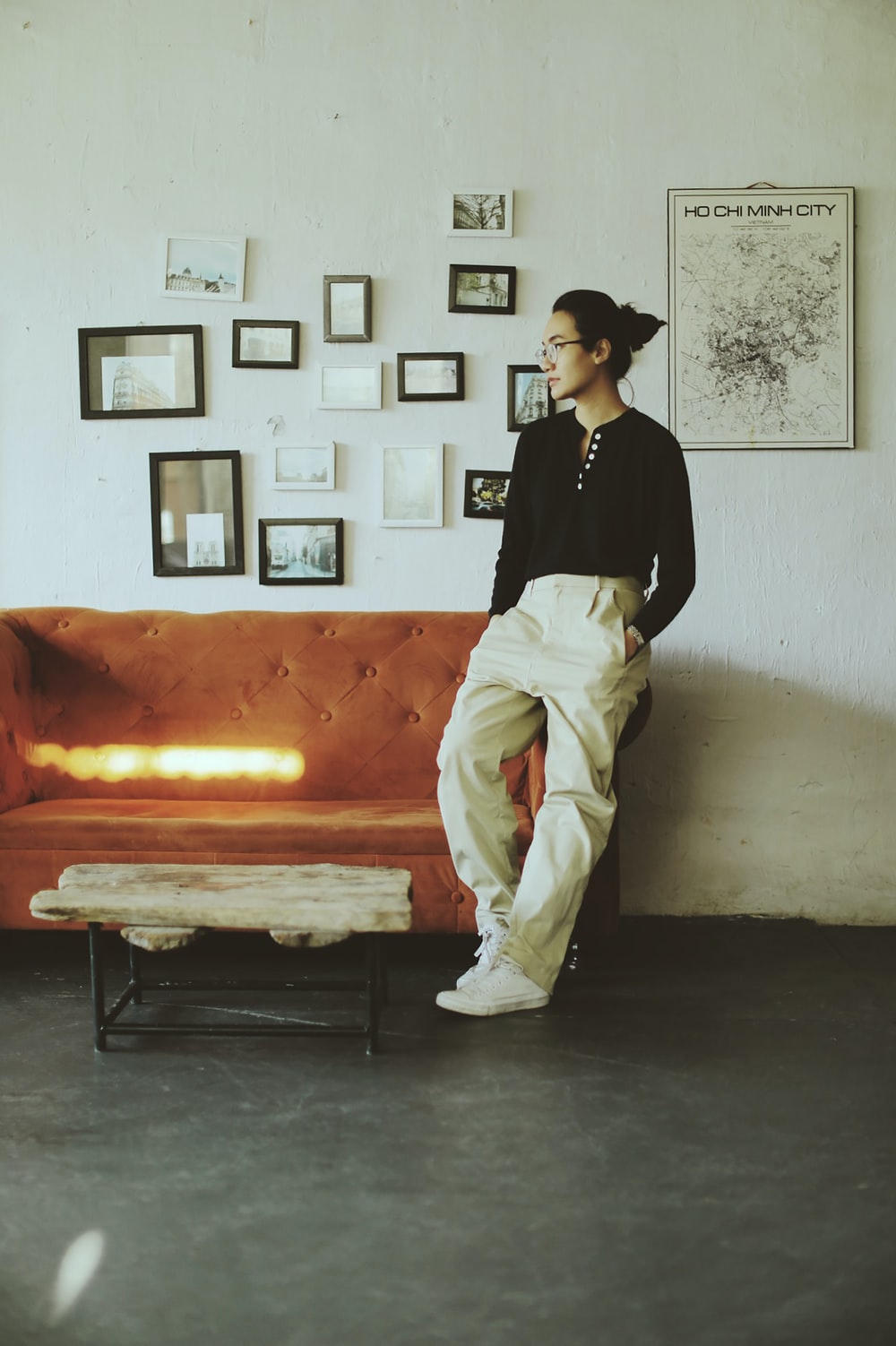 man in black long sleeve shirt and white pants sitting on orange bed