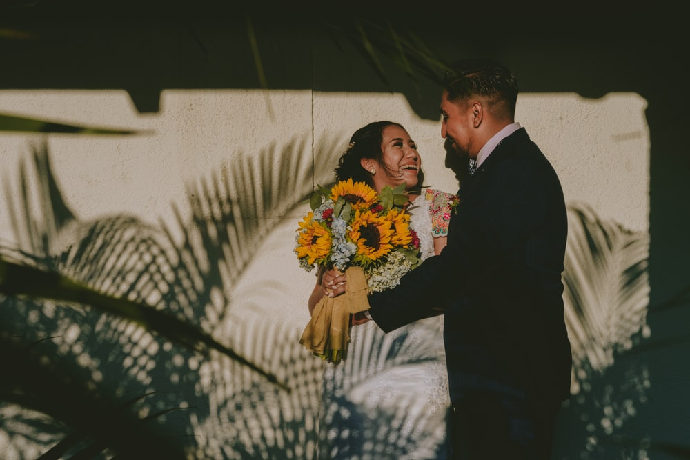 man in black suit jacket holding woman in white and blue floral dress