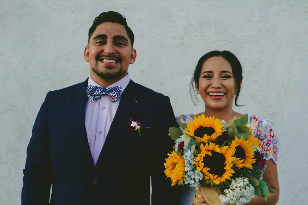 man in black suit standing beside woman in yellow and red floral dress