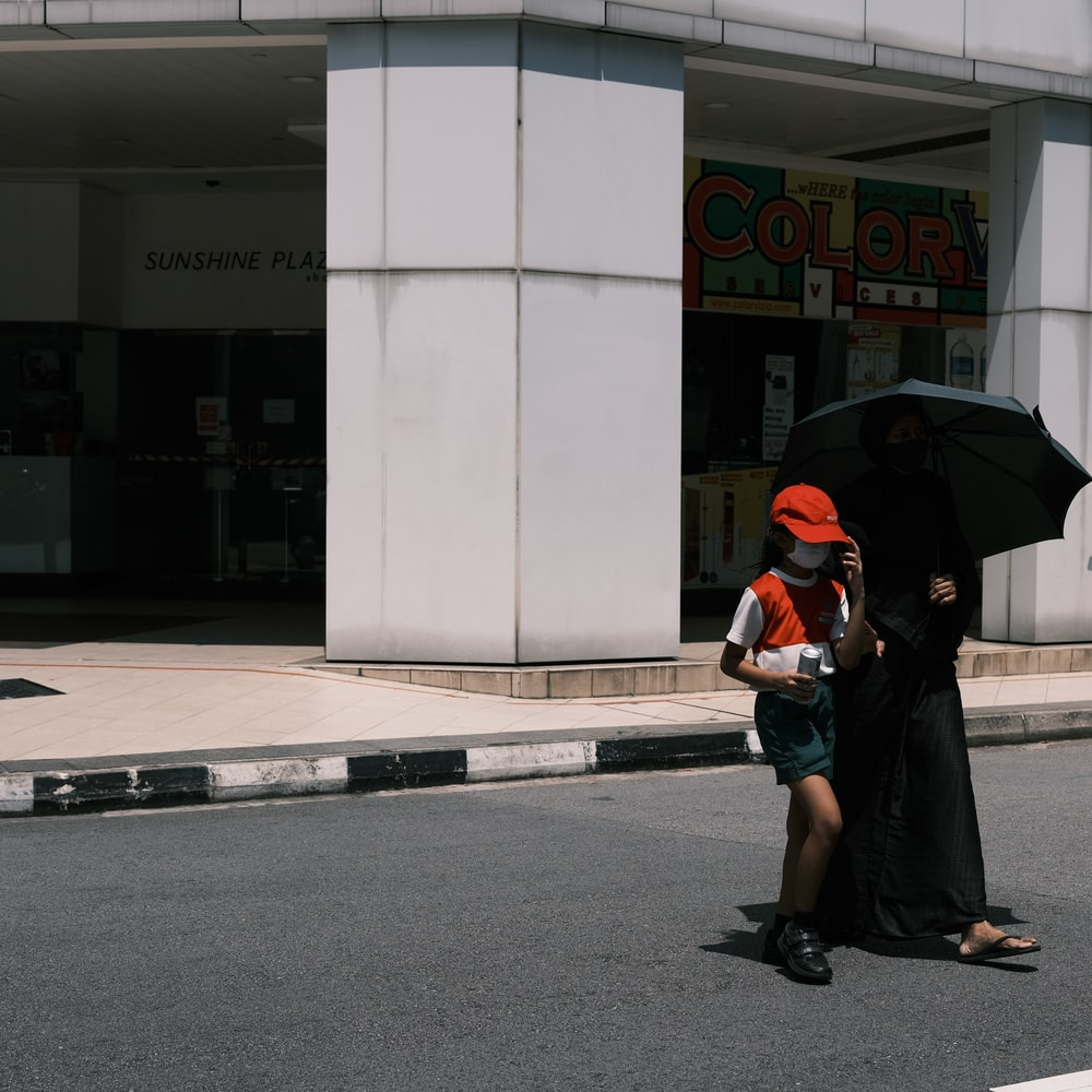 woman in black jacket and black skirt holding umbrella walking on sidewalk during daytime