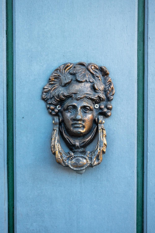 gold lion head bust on blue wooden door