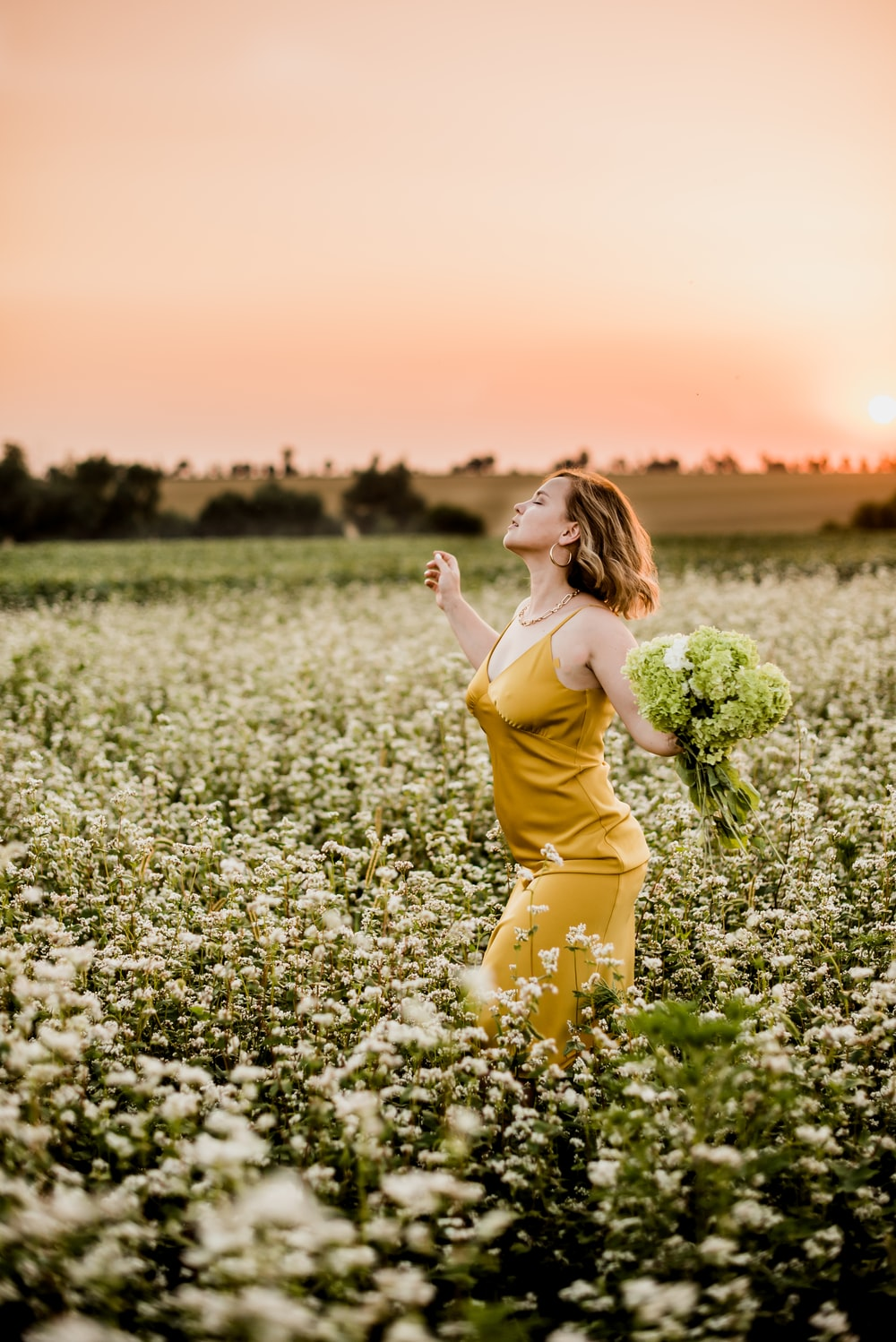 woman in yellow dress standing on flower field during daytime