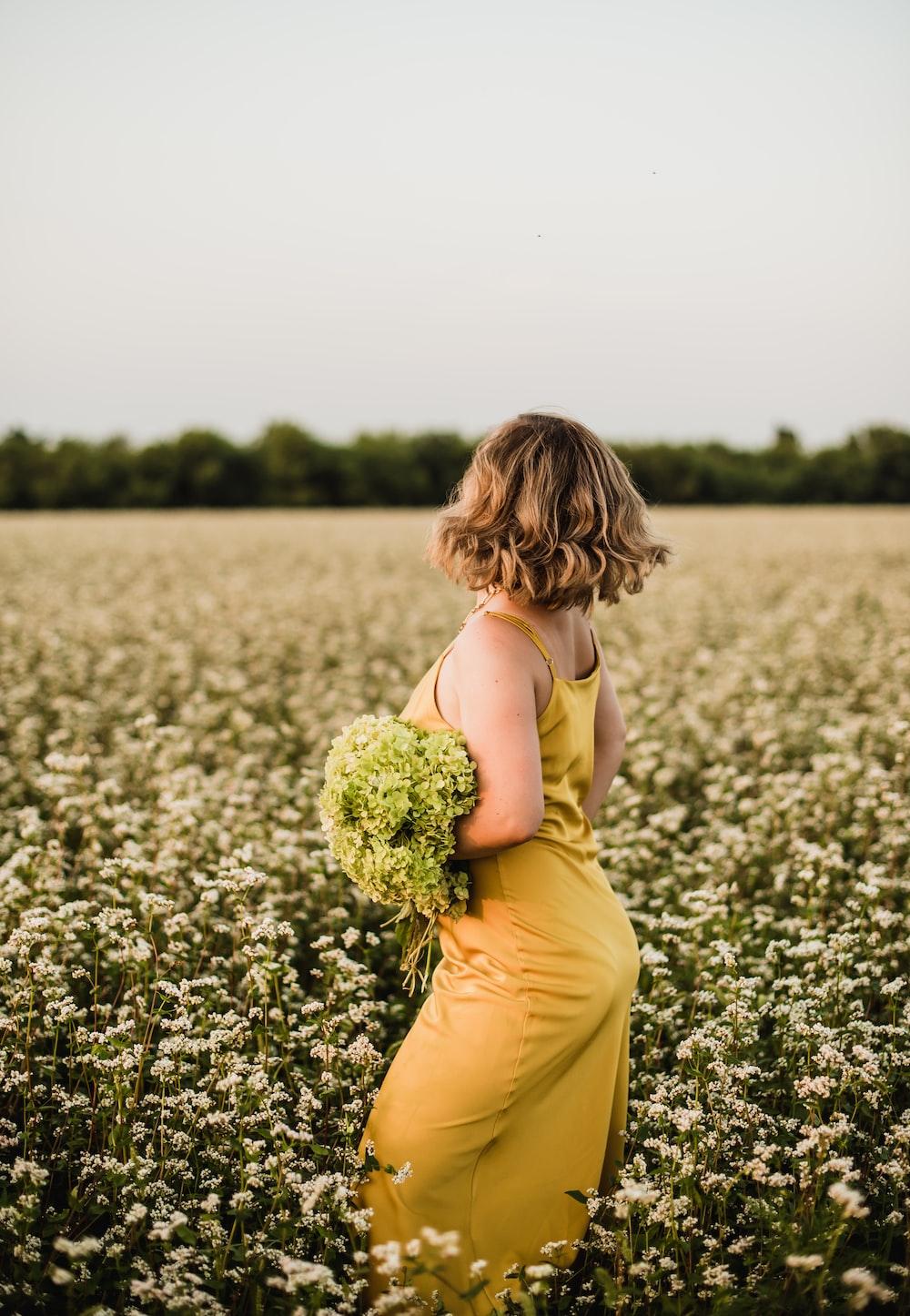 woman in yellow sleeveless dress holding yellow flower bouquet