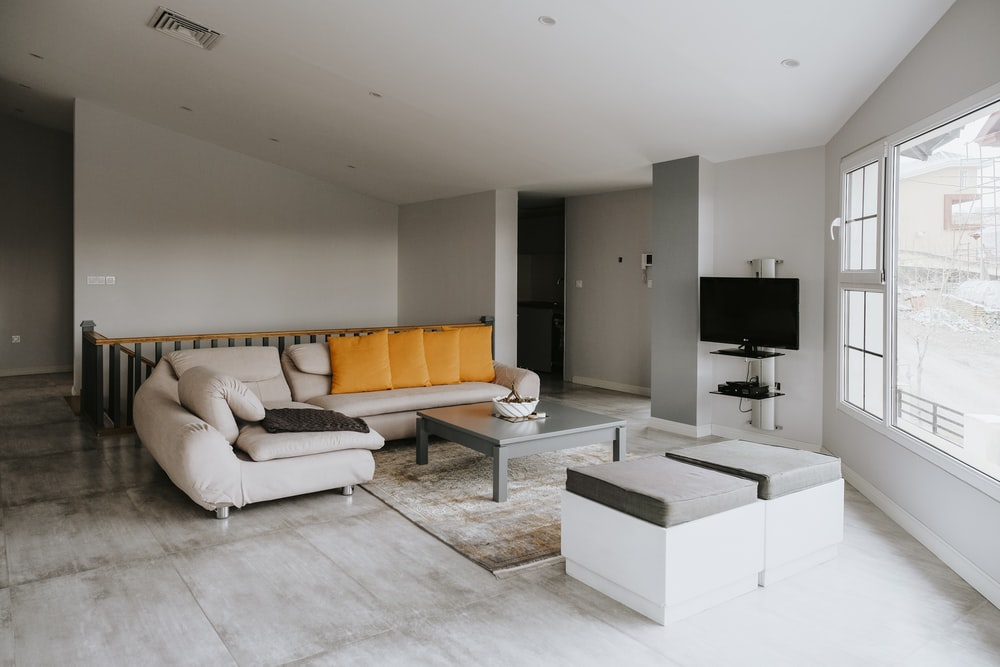 orange and white couch beside black flat screen tv