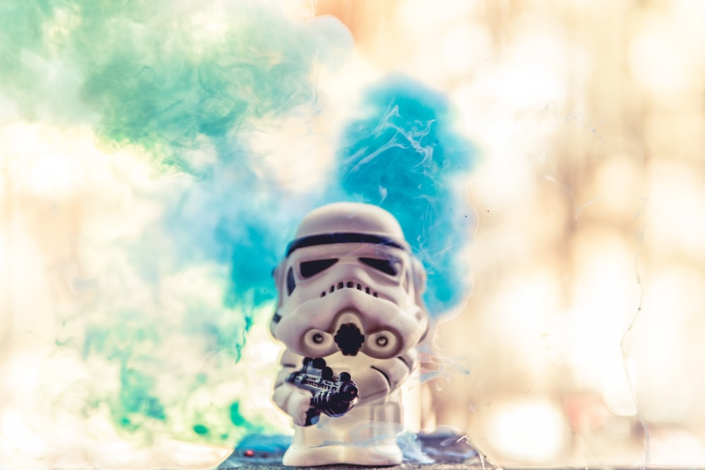 white and blue robot with blue smoke