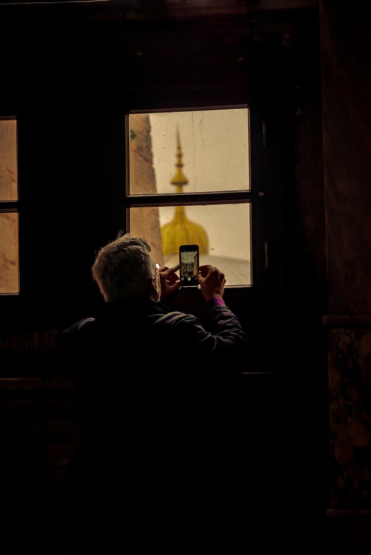 man in black jacket sitting on window during daytime